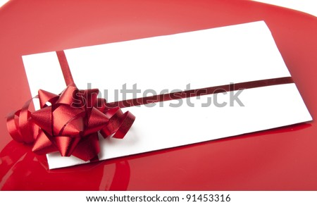 close up of a white envelope with a red ribbon on a red background - stock photo