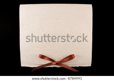 Close-up of a white parchment (diploma) with red ribbon on black background - stock photo