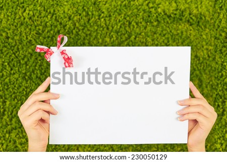 Close-up of a white sheet of paper holding by two woman hands with a red bow,ribbon in a corner isolated on green background. - stock photo