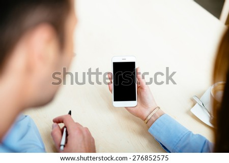 Close-up of a white smartphone held by a female hand - stock photo