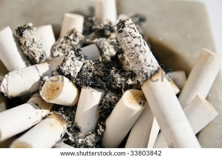 Close-up of a white stone square ashtray that is full of burnt cigarettes - stock photo