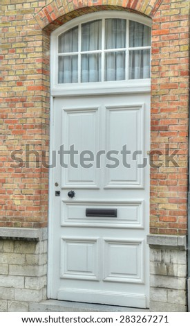 Close up of a white wooden door with a brick wall - stock photo