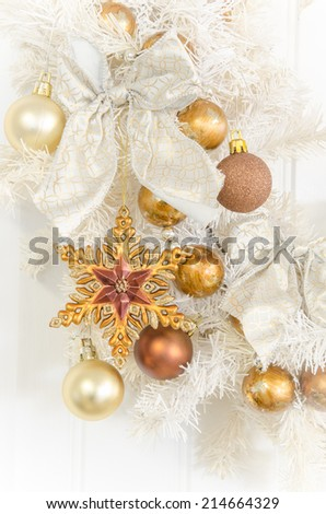 Close up of a white wreath with gold ornaments