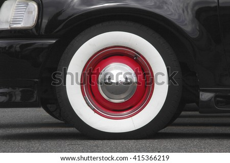 close up of a whitewall tyre with red trim and a silver reflective hubcap