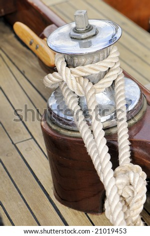 Close-up of a winch on a wooden sailboat - stock photo