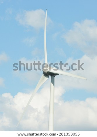 Close up of a wind turbine with a blue sky and clouds in the background - stock photo