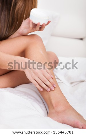 Close-up Of A Woman Applying Lotion On Her Feet