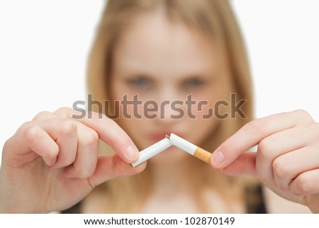 Close up of a woman breaking a cigarette against white background - stock photo