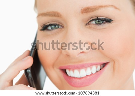 Close up of a woman calling with her smartphone against white background
