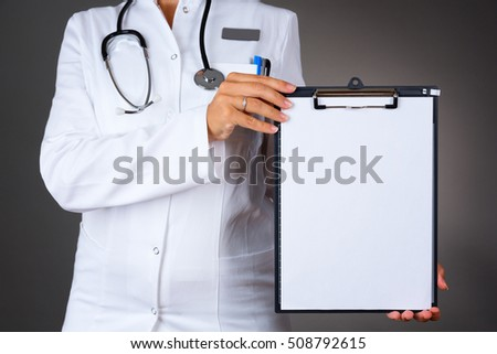 Close up of a woman doctor, holding a blank paper, isolated on dark background.