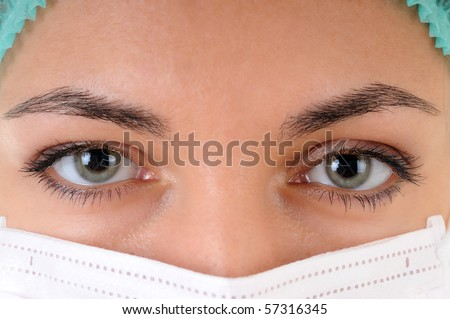 Close-up of a woman doctor's eye wearing a mask examining you. - stock photo
