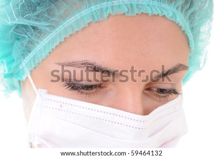 Close-up of a woman doctor's eye wearing a mask is looking down. - stock photo