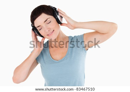 Close up of a woman enjoying some music against a white background