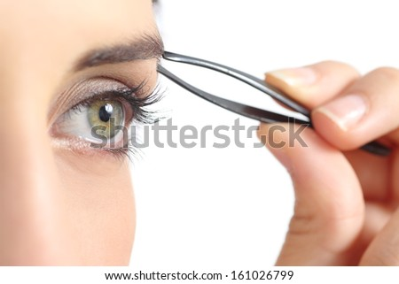 Close up of a woman eye and a hand plucking eyebrows isolated on a white background              - stock photo