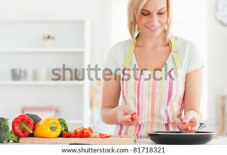 Close up of a woman frying peppers in the kitchen