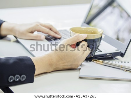 Close up of a woman hand holding a cup of coffee while  typing in a laptop on the office desk