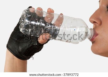 Close up of a woman hand holding and drinking from a clear water bottle - stock photo