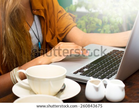 Close up of a woman hands typing in a laptop in a coffee shop