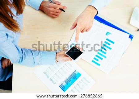 Close-up of a woman holding a mobile over a desk - stock photo