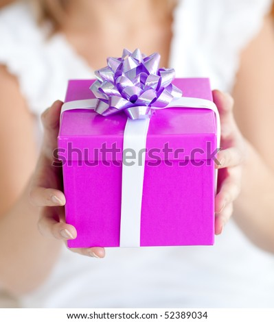 Close-up of a woman holding a present sitting on the floor at home - stock photo