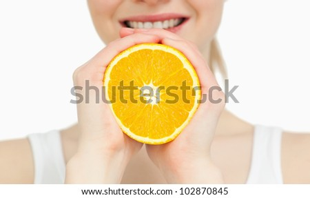 Close up of a woman holding an orange against white background