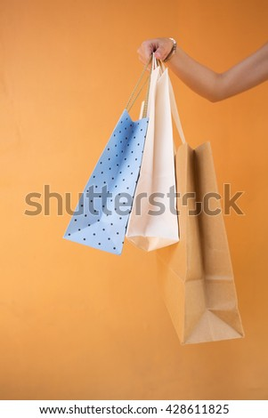 Close up of a woman holding shopping bags in front of an orange wall. - stock photo