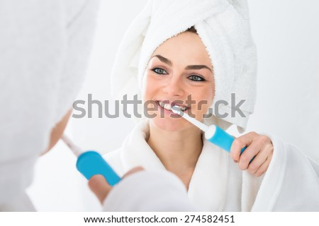 Close-up Of A Woman In Bathrobe Brushing Teeth - stock photo