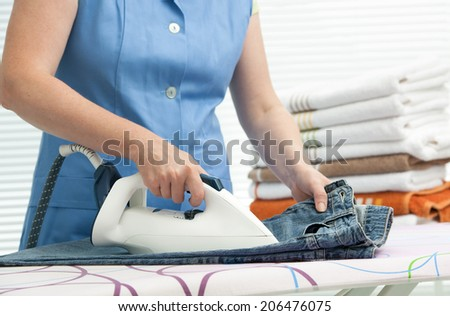 Close up of a woman ironing clothes with a steam iron - stock photo