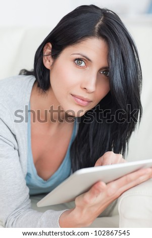 Close up of a woman laying on a couch while typing on a tablet in a living room