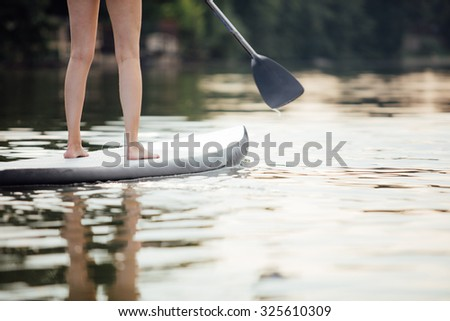 close-up of a woman legs on paddle board in water - stock photo