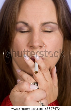 Close up of a woman lighting a cigarette with lighter - stock photo