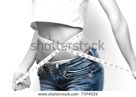 close up of a woman measuring her waist, b/w toned - stock photo