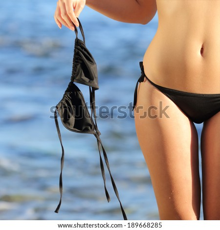 Close up of a woman on the beach in topless holding the bikini with the blue water in the background             - stock photo