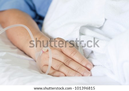 Close up of a woman patient in hospital with saline intravenous (iv) - stock photo