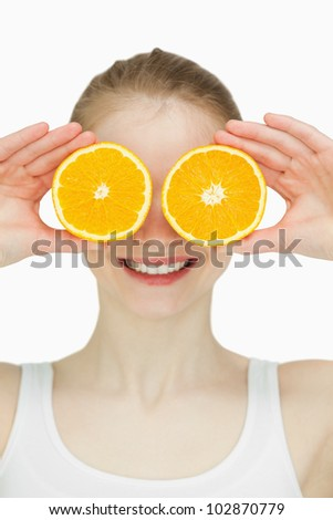 Close up of a woman placing oranges on her eyes against white background - stock photo