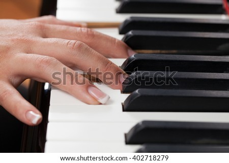 Close up of a woman playing piano.