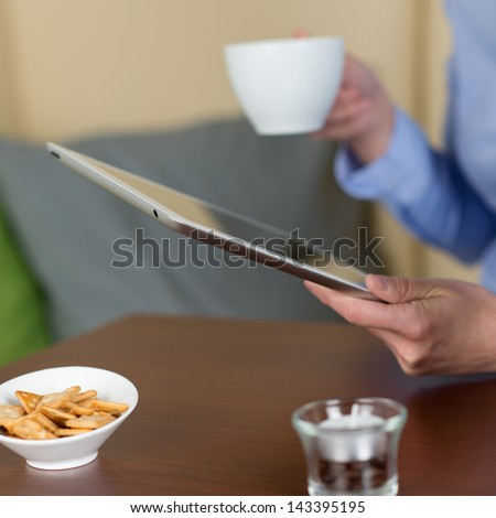 Close-up of a woman reading from a tablet in the coffee shop while drinking a cup of coffee - stock photo