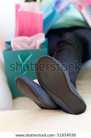 Close-up of a woman relaxing on her sofa after shopping - stock photo