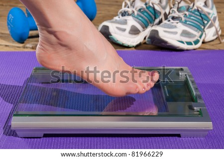 Close up of a woman's bare foot stepping on to a scale. - stock photo