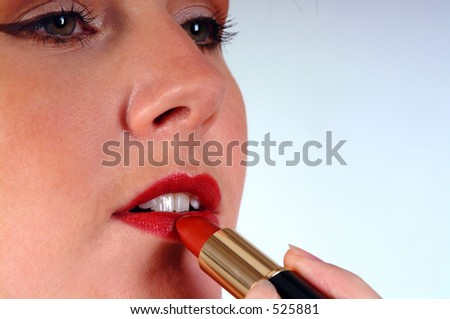 Close up of a woman's face as she puts on red lipstick. Shot against a white background with space on the right for text etc. - stock photo