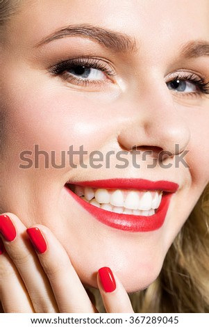 Close-up of a woman's face with a smile and a neat manicure