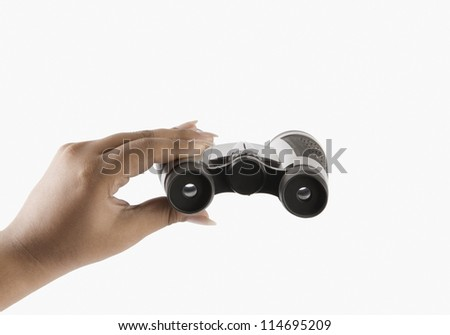 Close-up of a woman's hand holding binoculars - stock photo