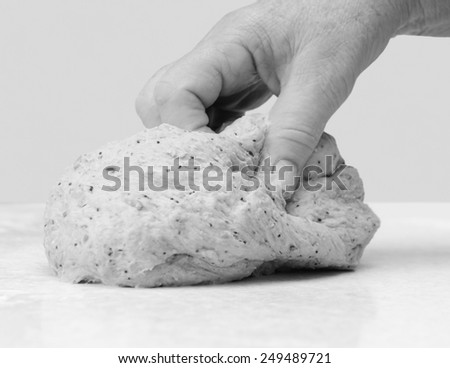Close-up of a woman's hand kneading multi seed bread dough on a kitchen worktop - monochrome processing - stock photo