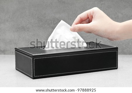 Close up of a woman's hand pulling a facial tissue from a black tissue box - stock photo