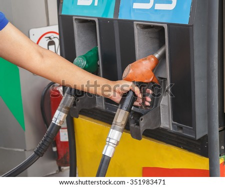 Close-up of a woman's hand using a fuel nozzle at a gas station. Petrol station. Filling station. Petrol. Gasoline.
