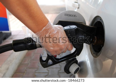 Close-up of a woman's hand using a petrol pump to fill his car up with fuel