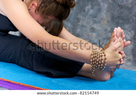 Close up of a woman's hands and feet as she bends over in a yogic forward fold or Paschimottasana on yoga mat in studio wearing mala beads.