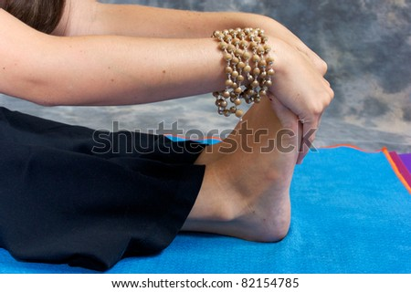 Close up of a woman's hands and feet as she bends over in a yogic forward fold or Paschimottasana on yoga mat in studio wearing mala beads. - stock photo