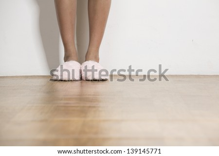 Close up of a woman's pink Fluffy slippers standing next to a white wall - stock photo