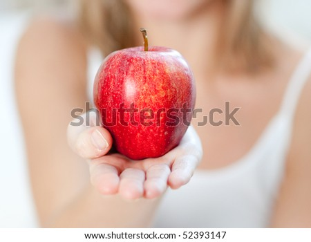 Close-up of a woman showing an apple at home